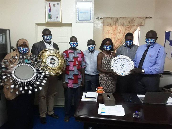A mini-grant beneficiary presents a decorative wall clock to #NACCUG